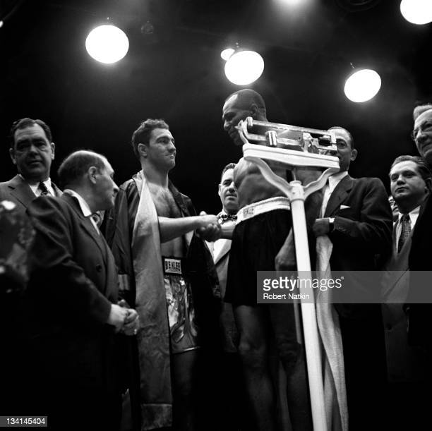 View of heavyweight boxers Rocky Marciano and Jersey Joe Wolcott shaking hands at their weigh-in, prior to their rematch, Chicago, 1953.