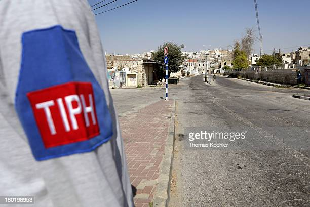 A view of Hebron and the sleeve of bearing the logo of Temporary International Presence in Hebron or TIPH is the civilian observer mission worn by...