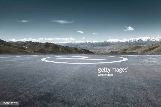 view of helipad with mountains range on background, haibei, qinghai, china - image stockfoto's en -beelden
