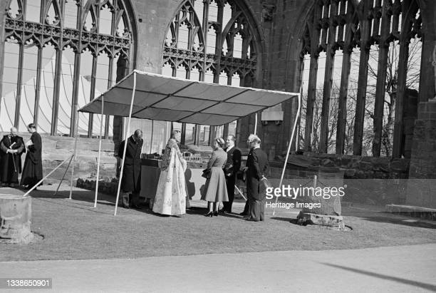 View of Her Majesty the Queen and the Duke of Edinburgh with the architect Basil Spence and Provost Howard, standing in the ruins of the old...