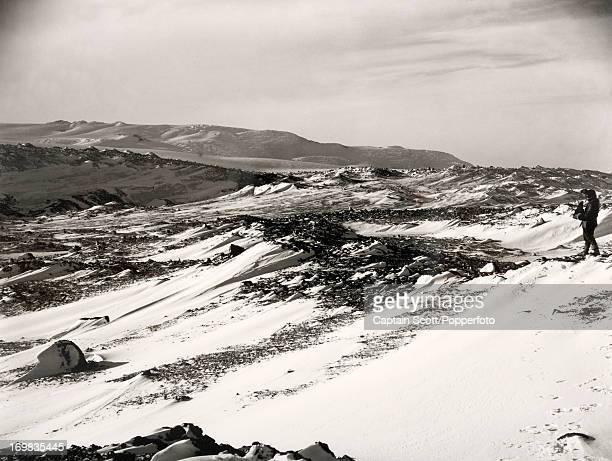 A view of Herbert Ponting working on the lower slopes of Mount Erebus photographed during the last tragic voyage to Antarctica by Captain Robert...