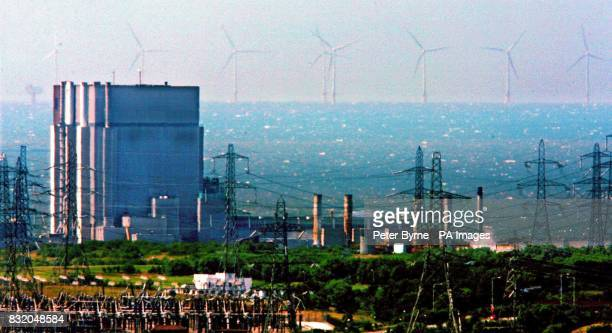 A view of Heysham Nuclear Power Station with electricity pylons in the foreground and wind turbines in the distance