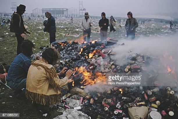 View of hippies and festival goers sitting and standing around a large bonfire of burning rubbish and drinks cans in a field of discarded rubbish in...