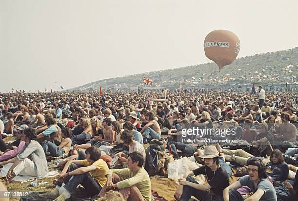 View of hippies and members of the audience pictured sitting on the grass waiting for bands to play on the stage at the Isle of Wight Festival 1970...