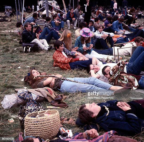 View of hippies and teenagers relaxing whilst sitting and lying on grass in front of a stage at a 'LoveIn' at the Festival of the Flower Children in...