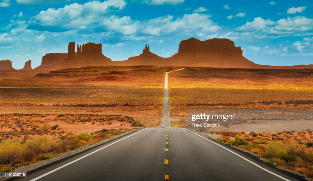 View of historic U.S. Route 163 running through famous Monument Valley in beautiful golden evening light at sunset on a beautiful sunny day with blue sky in summer, Utah, USA : Stock Photo