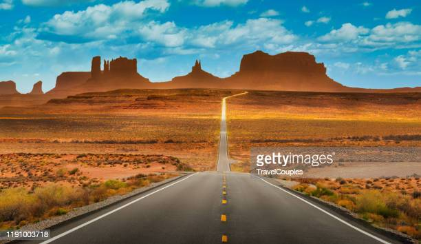 view of historic u.s. route 163 running through famous monument valley in beautiful golden evening light at sunset on a beautiful sunny day with blue sky in summer, utah, usa - utah stock pictures, royalty-free photos & images