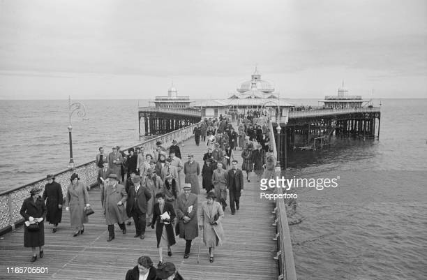 View of holidaymakers strolling along the pier as they enjoy a wartime vacation at the seaside resort town of Llandudno Wales during World War II in...