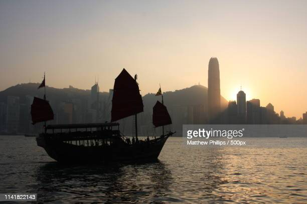 view of hong kong island across victoria harbour - hong kong stock pictures, royalty-free photos & images