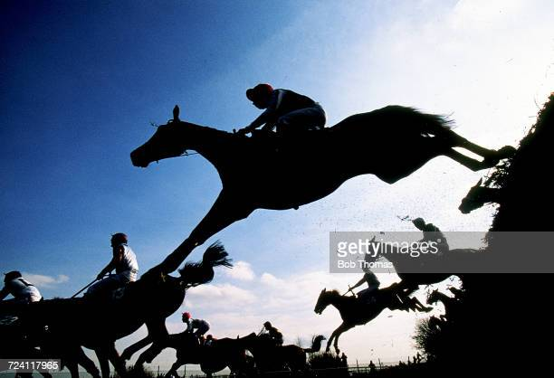 View of horses and riders clearing a fence during the 1995 Martell Grand National horse race at Aintree racecourse near Liverpool England on 8th...