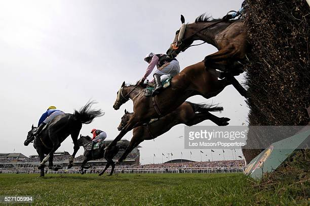 View of horses and riders clearing a jump as they compete in the 2010 Mersey Novices' Hurdle race at Aintree racecourse near Liverpool on 10th April...