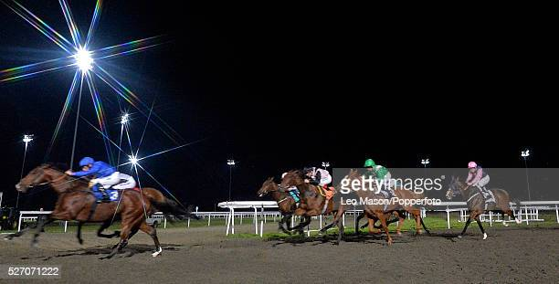 View of horses and riders competing in the Download The Bet Victor Instabet App Handicap flat race during a race meeting under floodlights at Kempton...