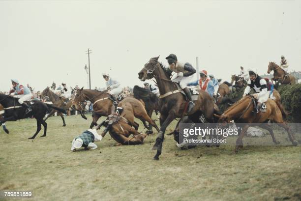 View of horses and riders jumping and falling at Becher's Brook fence during the 1987 Seagram Grand National steeplechase horse race at Aintree...