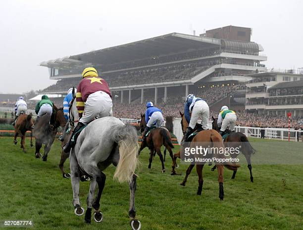 View of horses and riders on the first circuit competing in the 141st Year Of The National Hunt Chase Challenge Cup during the Cheltenham National...
