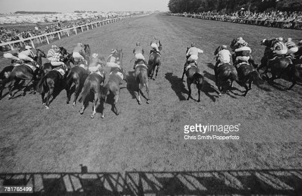 View of horses and riders racing out of the starting stalls at the start of the 1977 Epsom Derby at Epsom Downs Racecourse in Surrey, England on 1st...