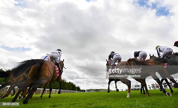 View of horses and riders racing out of the starting stalls during competition in the Qatar King George Stakes at the Qatar Goodwood Festival at...