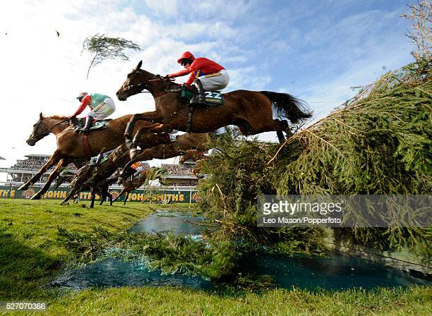 View of horses clearing a water fence in The Topham Steeplechase during the 2008 John Smith's Grand National Meeting at Aintree racecourse in...