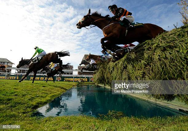 View of horses clearing a water jump fence in The Topham steeplechase during the 2008 John Smith's Grand National Meeting at Aintree racecourse in...