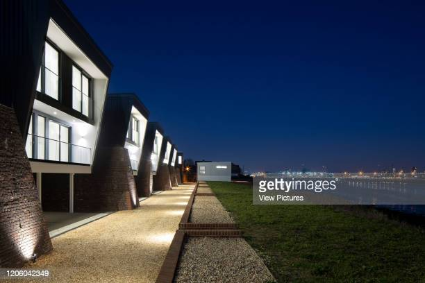 View of houses and historic dockyard in background at dusk. Priddys Hard, Gosport, United Kingdom. Architect: John Pardey Architects, 2019.