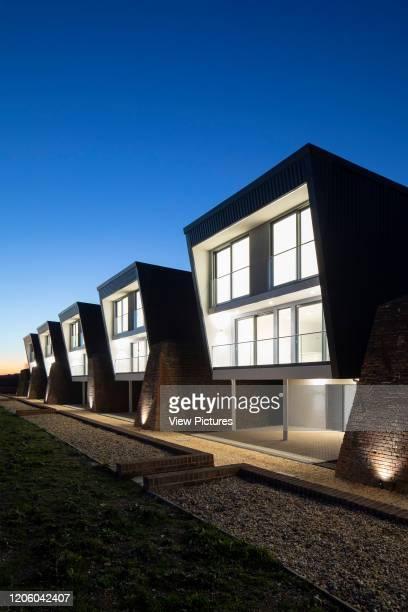 View of houses at dusk. Priddys Hard, Gosport, United Kingdom. Architect: John Pardey Architects, 2019.