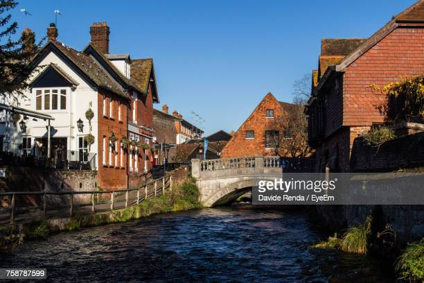 view of houses by river against clear sky - winchester hampshire stock photos and pictures