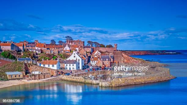 view of houses in sea against cloudy sky - fife scotland stock pictures, royalty-free photos & images