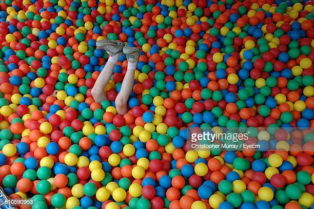 View of human legs amid colorful balls
