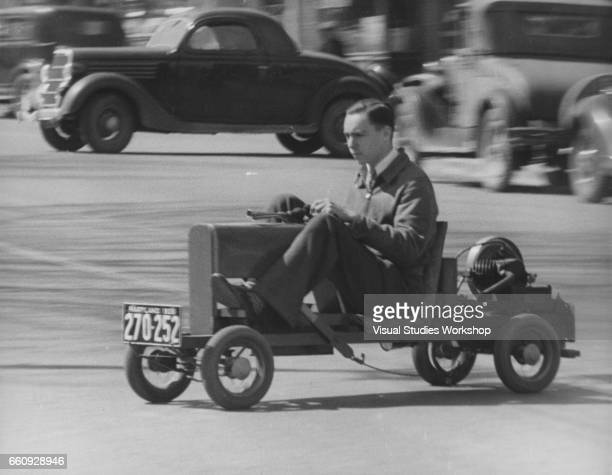 View of Humphrey Cissel as he steers his homebuilt 'midget auto' Rockville Massachusetts 1920s or 1930s The vehicle which cost three dollars to build...