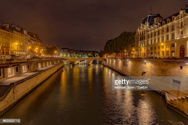 view of illuminated bridge over river at night - paris dunn stock photos and pictures