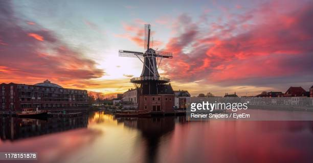 view of illuminated buildings against sky during sunset - haarlem fotografías e imágenes de stock