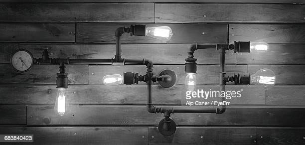 view of illuminated bulbs on pipe against wall - industrial revolution stock pictures, royalty-free photos & images