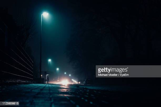 view of illuminated street at night - luce stradale foto e immagini stock