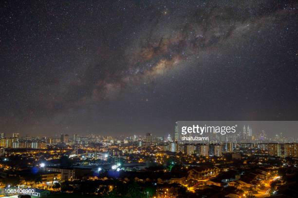 View of image composite of Milky Way over downtown Kuala Lumpur, Malaysia.