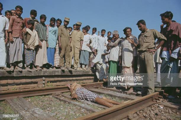 View of Indian army troops and local civilians looking at the bound body of a man found shot on a railway line near the East Pakistan town of Jessore...