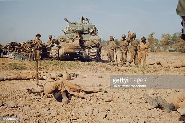 View of Indian soldiers standing either side of a Sherman tank observing corpses of dead soldiers after a battle in a disputed border area between...