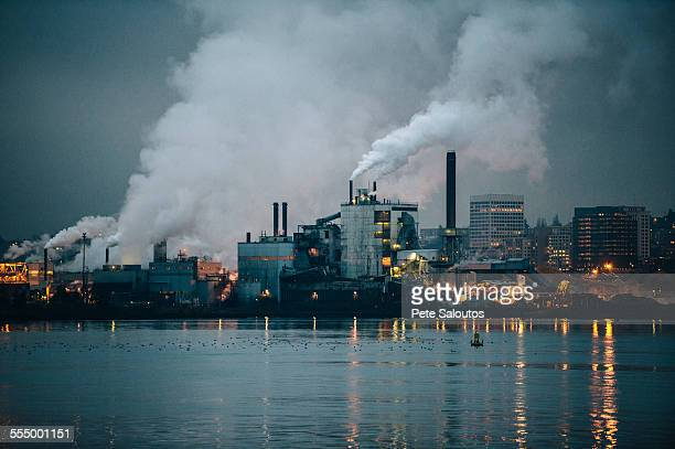 view of industrial plant and smoke stacks at night, tacoma, washington, usa - distrito industrial - fotografias e filmes do acervo