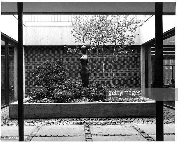 View of internal courtyard, with a sculpture and landscaped trees and shrubbery, in the Milton S Eisenhower library of Johns Hopkins University, in...