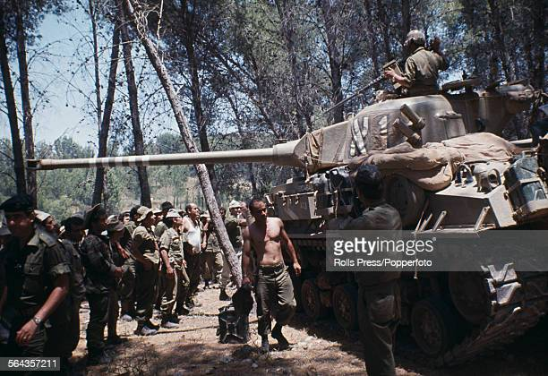 View of Israeli troops and members of the Israel Defense Forces pictured under cover with a Super Sherman tank in a wooded area overlooking the...