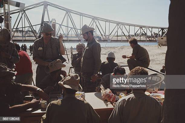 View of Israeli troops and members of the Israel Defense Forces eating a meal at tables beside the Suez Canal after advancing across the Sinai...