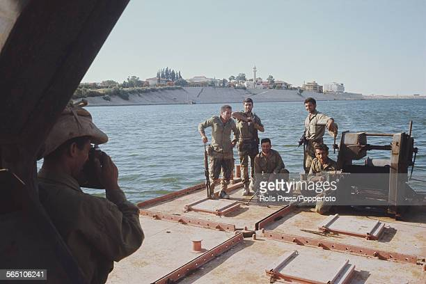 View of Israeli troops and members of the Israel Defense Forces posing for a photograph on a platform beside the Suez Canal after advancing across...