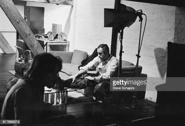 View of Italian film director Michelangelo Antonioni on the set of his film 'BlowUp' London England 1965 The woman at fore is unidentified