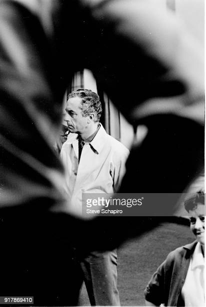 View of Italian film director Michelangelo Antonioni seen through the arm of an unidentified crewmember on the set of his film 'BlowUp' London...