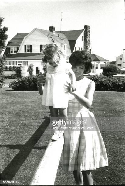 View of Jacqueline Kennedy as she helps her daughter Caroline balance on a pole Hyannis Port Massachusetts Summer 1960