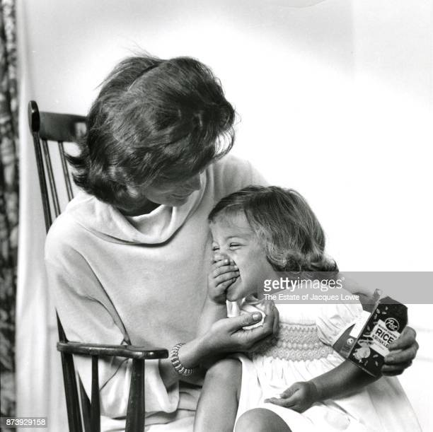View of Jacqueline Kennedy as she holds her daughter Caroline as the latter eats cereal Hyannis Port Massachusetts Spring or Summer 1959 The photo...