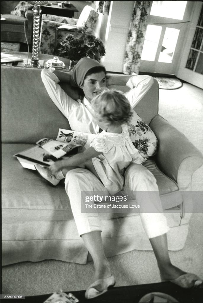 Jackie relaxes with her daughter Caroline on her lap in Massachusetts