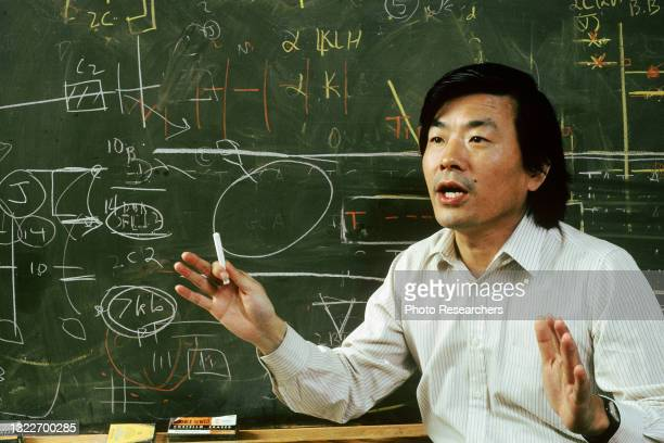 View of Japanese geneticist and neuroscientist Dr Susumu Tonegawa, a piece of chalk in his hand, as he lectures in front of a blackboard at the...