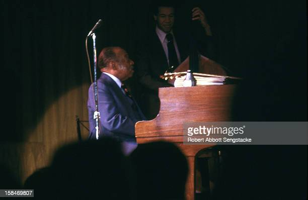 View of jazz pianist, composer, and big band leader William 'Count' Basie performing on the piano with his band, 1985.