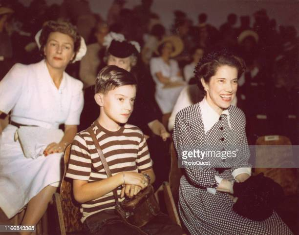View of Jean MacArthur and her son Arthur MacArthur IV sit in a reviewing stand during the US Independence Day parade held at the Emperor's Palace...