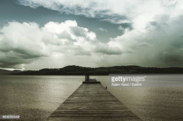 View Of Jetty Leading To Calm Sea Against Sky