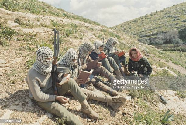 View of keffiyeh wearing Fatah guerilla recruits reading arabic translations of 'Quotations from Chairman Mao Tse-tung' whilst undergoing commando...